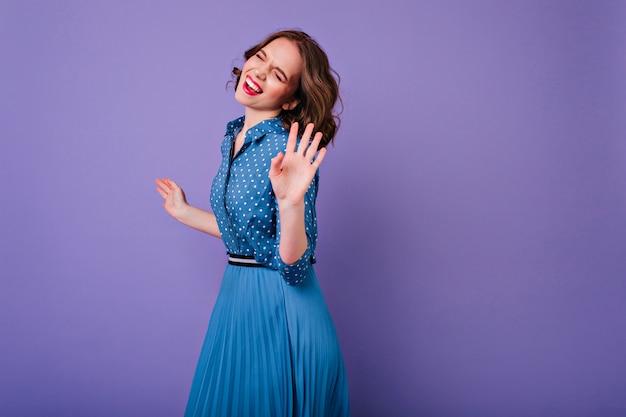 Niesamowita kaukaska dziewczyna w niebieskiej sukience vintage uśmiechnięta z zamkniętymi oczami elegancka młoda dama z krótką falującą fryzurą tańczącą na fioletowej ścianie.