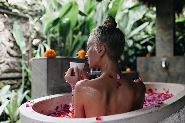 Niesamowita kobieta pije herbatę z zamkniętymi oczami siedząc w wannie. portret z tyłu wesoła dama z opaloną skórą robi spa z płatkami róż.