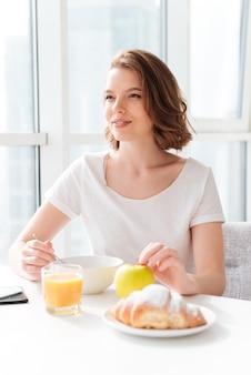 Niesamowita kobieta siedzi w pomieszczeniu przy stole z sokiem