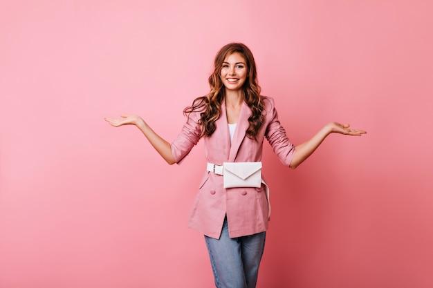 Niesamowita kobieta w eleganckim stroju casual stojąca na różowo. pełen wdzięku rudowłosa modelka uśmiecha się