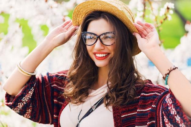 Niesamowita kobieta z jasnym makijażem, niebieskimi oczami, okularami, słomkowym kapeluszem pozuje w słonecznym wiosennym parku w pobliżu drzewa kwiatowego