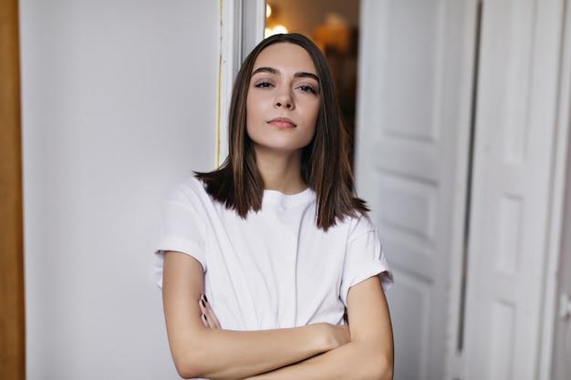 Niesamowita kobieta z nagim makijażem pozuje w swoim mieszkaniu. wewnątrz zdjęcie uroczej kaukaskiej kobiety stojącej z rękami skrzyżowanymi