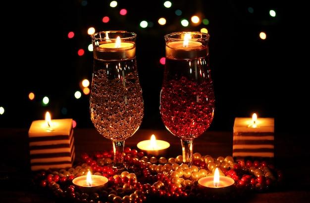 Niesamowita kompozycja świec i kieliszków na drewnianym stole z rozmytymi światłami