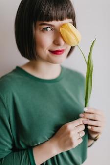 Niesamowita krótkowłosa dziewczyna na białym tle z żółtym kwiatem. zainteresowana kaukaska dama trzyma tulipana z uroczym uśmiechem.