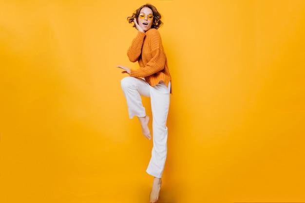 Niesamowita krótkowłosa kobieta w modnym swetrze stojąca na jednej nodze i podpierająca twarz ręką