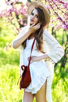 Niesamowita młoda atrakcyjna kobieta w białej lekkiej sukience z długimi włosami, w kapeluszu spaceru w słonecznym ogrodzie w okresie letnim. kwitnąca sakura, jasne kolory, patrząc w kamerę, stylowy wrażliwy model, zrelaksuj się