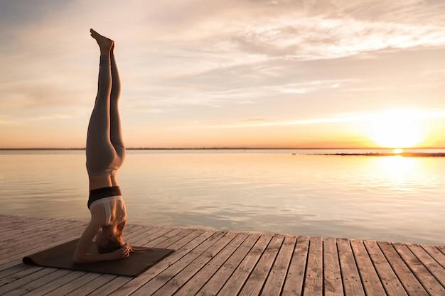 Niesamowita młoda dama sportowa wykonuje ćwiczenia jogi.