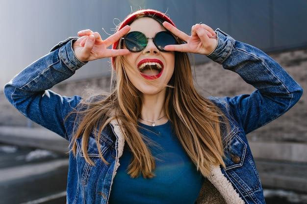 Niesamowita młoda dama w modnym stroju, śmiejąca się i robiąca znak pokoju. zewnątrz portret beztroskiej pozytywnej dziewczyny w okularach przeciwsłonecznych, zabawy.