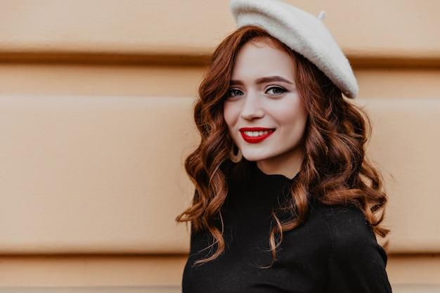 Niesamowita młoda dama we francuskim berecie cieszy się dobrym dniem. romantyczna kobieta w brązowym kapeluszu stojącym na zewnątrz.