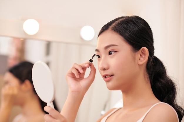 Niesamowita młoda kobieta robi makijaż przed lustrem. portret pięknej dziewczyny w pobliżu stołu kosmetycznego