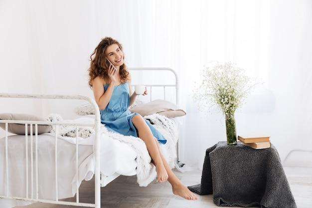 Niesamowita młoda kobieta siedzi w domu na łóżku i rozmawia przez telefon