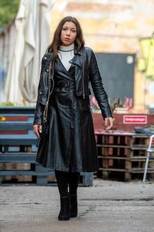 Niesamowita młoda kobieta w czarnych skórzanych ubraniach na nieostre kawiarni na świeżym powietrzu