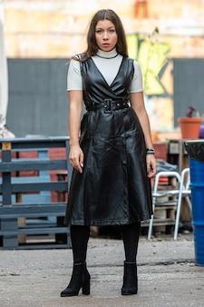 Niesamowita młoda kobieta w czarnych skórzanych ubraniach na rozmytym tle kawiarni na świeżym powietrzu