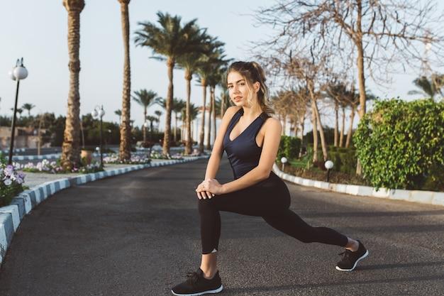 Niesamowita młoda kobieta w sporstwear rozciągająca się na ulicy w słoneczny poranek. patrzenie, aktywny tryb życia, wyrażanie pozytywności, trening, uprawianie sportu, joga, pracowita sporstwomanka