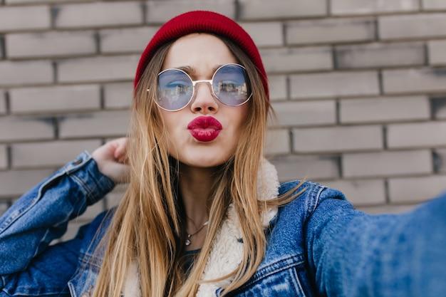 Niesamowita młoda kobieta z jasny makijaż pozowanie z całowaniem wyrazem twarzy. zbliżenie marzycielskiej blondynki wygłupiać się podczas robienia sobie zdjęcia.