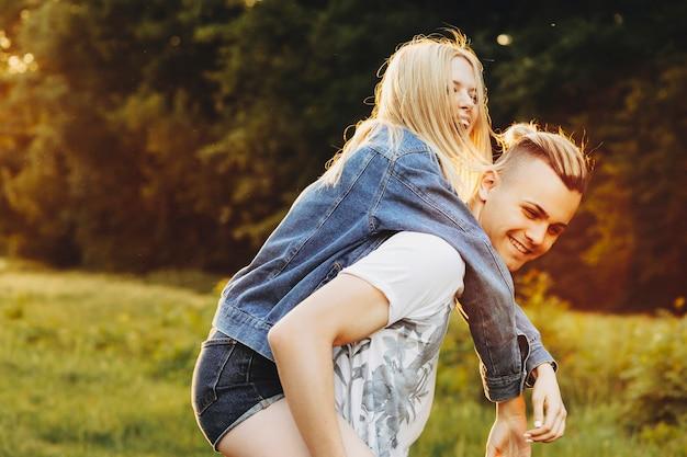 Niesamowita młoda para dobrze się bawi, podczas gdy dziewczyna jest na barana swojego chłopaka śmiejącego się na zewnątrz lasu.