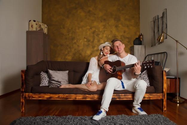 Niesamowita młoda para z gitarą we wnętrzu pokoju. śliczna kobieta i mężczyzna na kanapie z gitarą. koncepcja nauki w domu lub gry na gitarze w domu. miejsce objęte prawami autorskimi dla witryny, banera lub logo