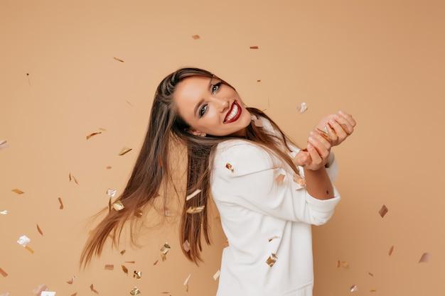 Niesamowita modelka z uroczym uśmiechem i długimi jasnobrązowymi włosami w białej kurtce pozuje na beżowej ścianie z confeti i przygotowuje się do przyjęcia urodzinowego