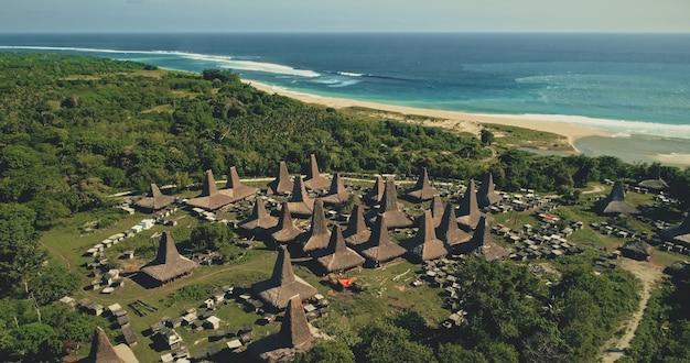 Niesamowita nadmorska tradycyjna wioska z unikalnie zaprojektowanymi dachami mieści widok z lotu ptaka. atrakcją turystyczną indonezji w zielonej dolinie z drzewami zwrotnikowymi w pobliżu zatoki oceanicznej. filmowy widok z drona