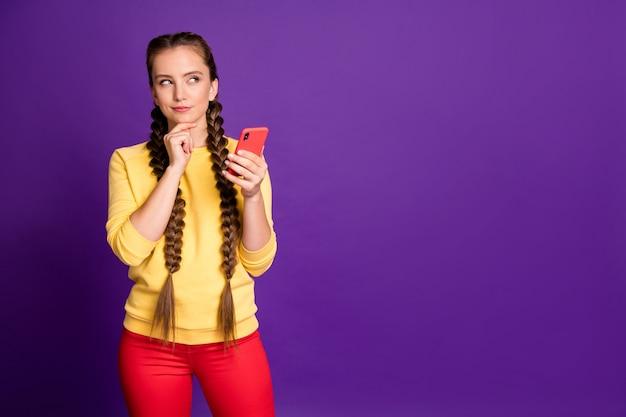 Niesamowita nastolatka trzymająca telefon, wyglądająca na pustą przestrzeń, ma kreatywną myśl o nowym postu na co dzień żółty sweter czerwone spodnie na białym tle fioletowa ściana