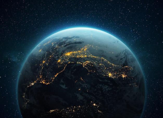 Niesamowita niebieska planeta ziemia z nocnymi żółtymi światłami megamiast w kosmosie z gwiazdami. głęboka przestrzeń z planetą. koncepcja cywilizacji. miasta europy środkowej