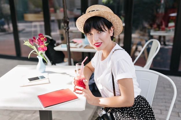 Niesamowita niebieskooka dziewczyna o ciemnych włosach pod słomkowym kapeluszem odpoczywa w kawiarni przy stole z notatnikiem, telefonem i kwiatami