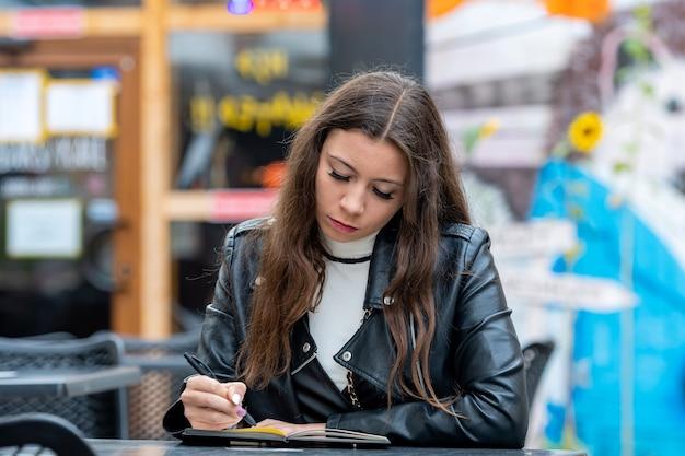 Niesamowita optymistyczna młoda kobieta z długimi włosami, robienie notatek w notatniku, siedząc w kawiarni na świeżym powietrzu