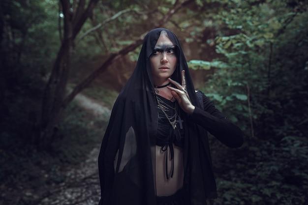 Niesamowita oszałamiająca dziewczyna w czarnej sukience. fotografia artystyczna. piękna łysa kobieta w mistycznej scenerii