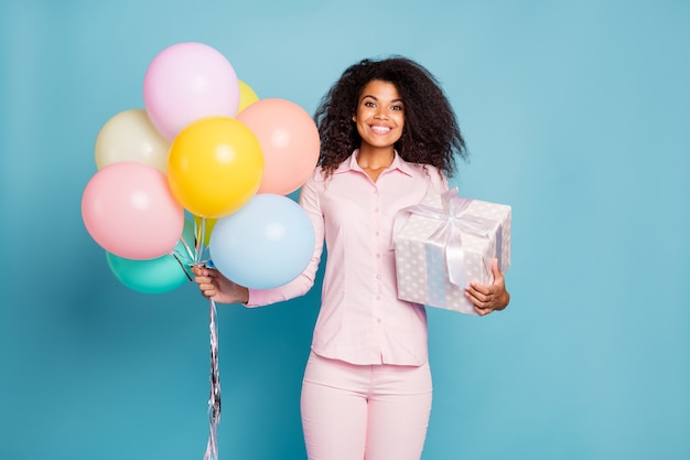 Niesamowita pani trzymająca duże zapakowane pudełko upominkowe i wiele kolorowych balonów