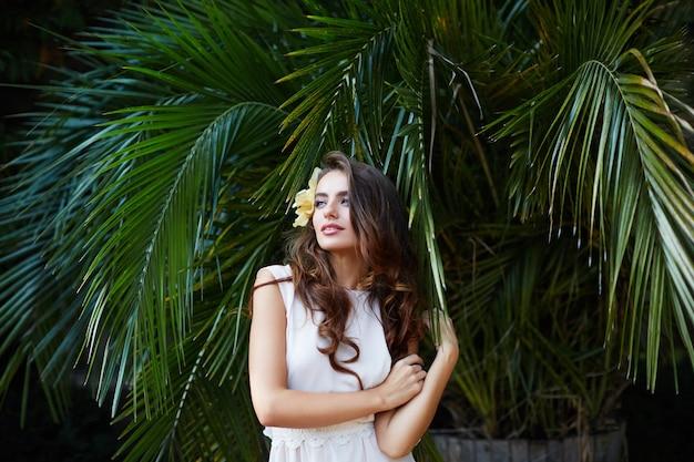 Niesamowita panna młoda z długimi kręconymi włosami w sukni ślubnej na tle zielonych liści, fotografia ślubna, portret.