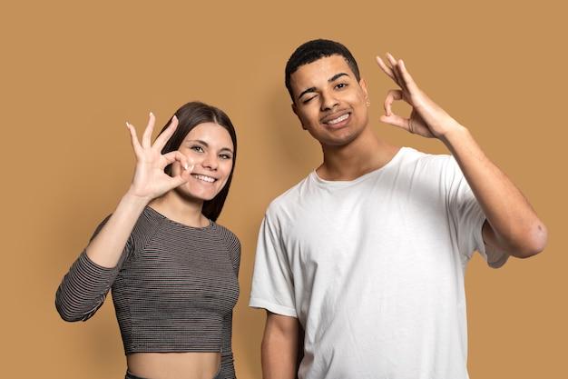 Niesamowita para małżeńska przedstawiająca symbole okey zgadza się z dobrą jakością produktu nosić swobodny strój na białym tle brązowy