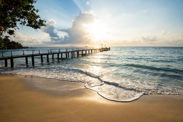 Niesamowita piaszczysta tropikalna plaża z sylwetka drewnianym mostem na plaży