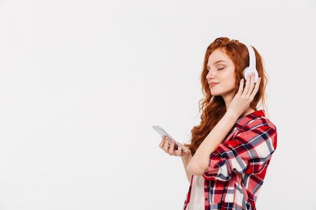 Niesamowita piękna młoda ruda dama rozmawia i słucha muzyki