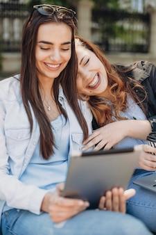 Niesamowita rudowłosa kobieta śmiejąca się z zamkniętymi oczami siedząc na ławce, opierając dłoń na swoim przyjacielu, który patrzy na ekran tabletu, śmiejąc się.