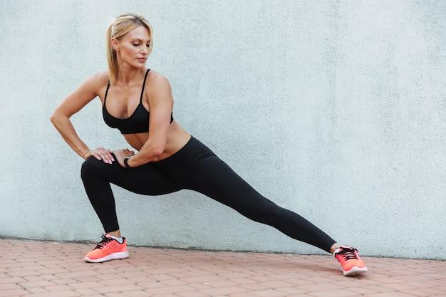 Niesamowita, silna młoda kobieta sportowa wykonuje ćwiczenia sportowe