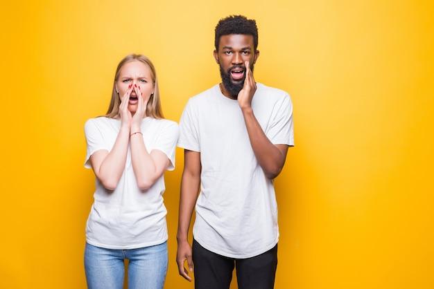 Niesamowita sprzedaż. zszokowana międzyrasowa para patrząca z przodu i dotykająca swoich policzków ze zdumieniem, pozująca razem na białym tle nad żółtą ścianą