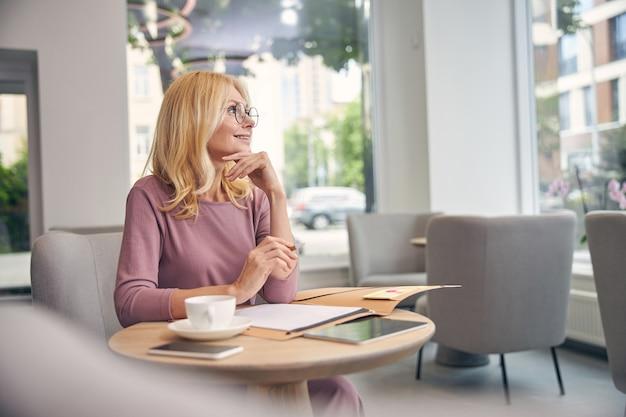 Niesamowita starsza kobieta trzymająca uśmiech na twarzy, patrząc w górę przez okno, będąc w kawiarni