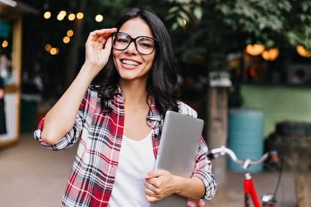 Niesamowita studentka w okularach stojąc na ulicy z uśmiechem. portret uroczej kobiety łacińskiej z laptopa.