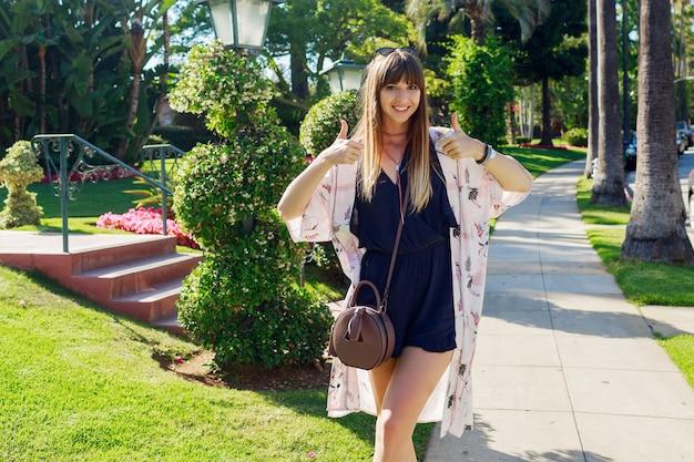 Niesamowita stylowa kobieta w niebieskim kostiumie i białym kimono ciesząca się wakacjami. ona się uśmiecha, pokazuje znaki.
