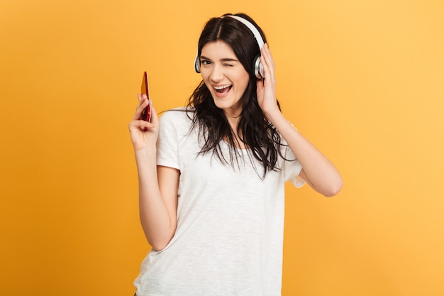 Niesamowita szczęśliwa młoda ładna kobieta słuchająca muzyki w słuchawkach.