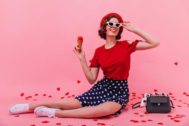 Niesamowita szczupła dziewczyna w spódnicy, jedzenie lodów. urocza kaukaska kobieta siedzi na podłodze i delektuje się deserem.