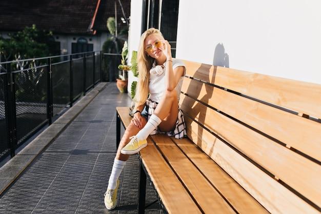 Niesamowita szczupła dziewczyna w żółtych butach pozowanie na drewnianej ławce. odkryty strzał opalonej blondynki kobiety w stroju casual, spędzania czasu w mieście.