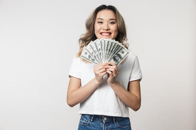 Niesamowita urocza młoda kobieta pozuje na białym tle nad białą ścianą trzymająca pieniądze