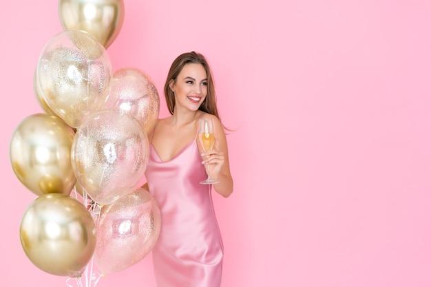 Niesamowita uśmiechnięta dziewczyna trzyma kieliszek szampana, a na imprezę przybyło wiele balonów powietrznych