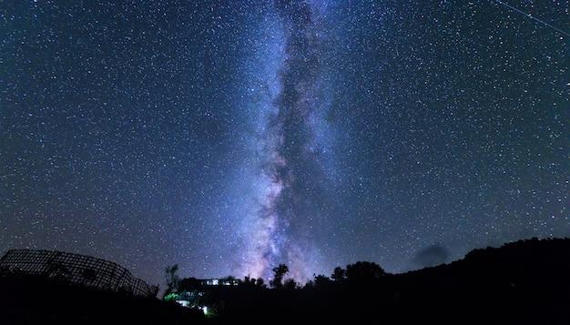 Niesamowita wiejska scena z gwiaździstym niebem w nocy