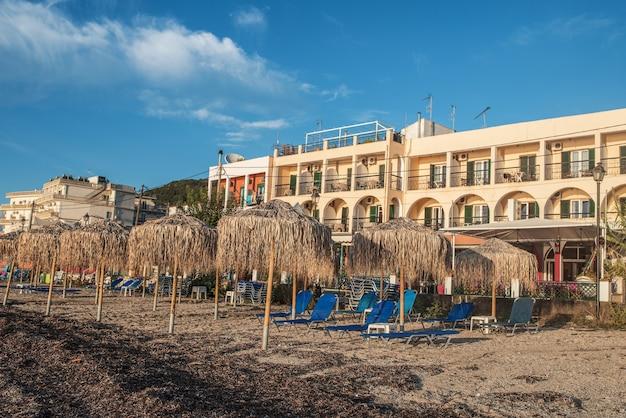 Niesamowita zatoka na wyspie korfu, grecja. piękny krajobraz plaży morza jońskiego z kolorowymi szezlongami, drzewami na zielonych górach i hotelami dla turystów.
