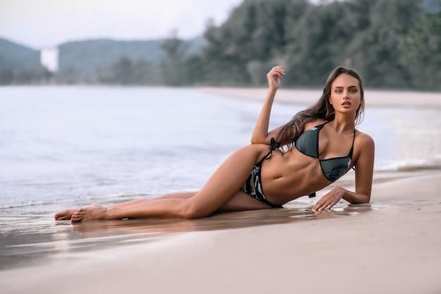 Niesamowita zmysłowa uwodzicielska kobieta siedzi i odpoczywa na plaży, ciesząc się wakacjami.