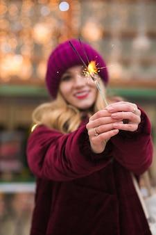 Niesamowite blondynka trzymając świecące światła bengalu na jarmarku bożonarodzeniowym w kijowie. efekt rozmycia