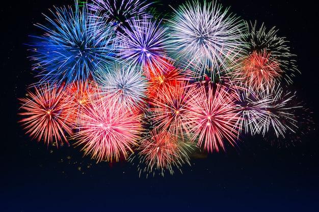 Niesamowite czerwone, złote, niebieskie fajerwerki nad nocnym niebem