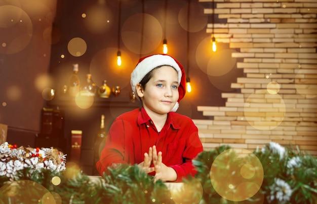 Niesamowite dziecko w czapce świętego mikołaja na rozmytym złotym tle
